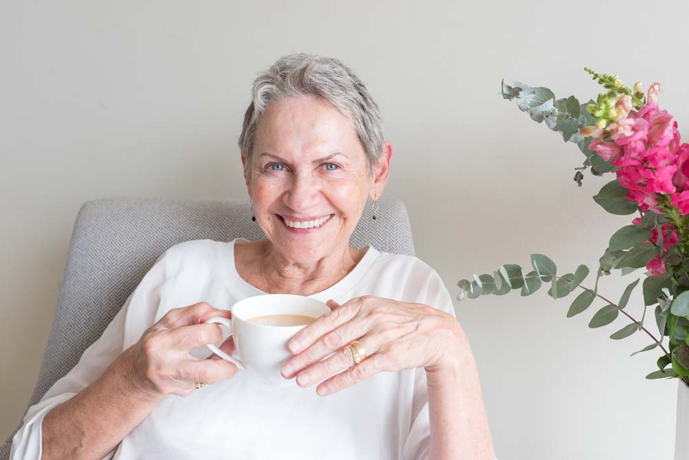 Closeup of beautiful senior woman holding tea cup